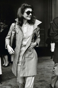 Jackie in a trench coat.